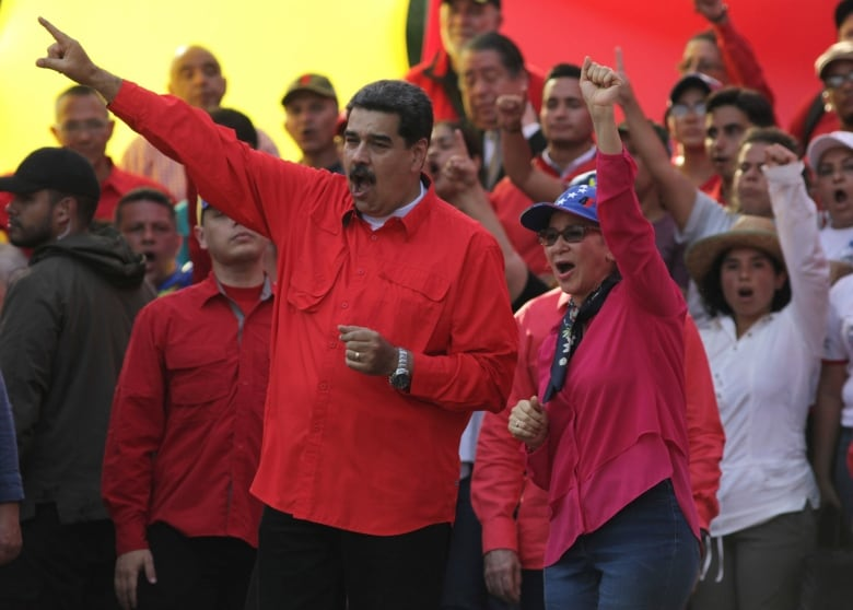 Maduro and his wife Cilia Flores, centre right, wave at supporters during a rally in Caracas Wednesday. (Boris Vergara/Associated Press)