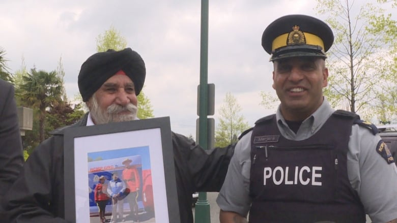 969409a7 Sukhdev Singh Brar poses with his portrait and an officer from the Surrey  RCMP. (Tina Lovgreen/CBC)