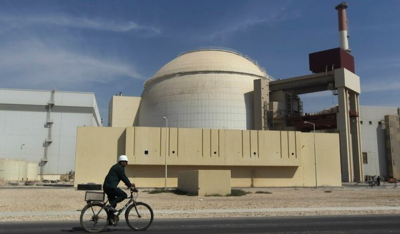 In this 2010 file photo, a worker rides a bike in front of the reactor building of the Bushehr nuclear power plant, outside Bushehr, Iran. (Majid Asgaripour/Mehr News Agency via Associated Press)