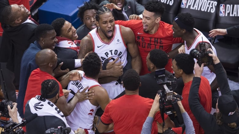 13558ba06 Toronto Raptors forward Kawhi Leonard celebrates with teammates after  making the buzzer-beating shot to defeat the Philadelphia 76ers in a  classic Game 7 on ...