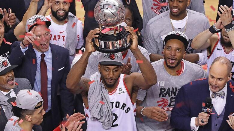 b9215950e Raptors forward Kawhi Leonard nearly cracks a smile while hoisting the NBA  Eastern Conference championship trophy on Saturday night following a 100-94  win ...