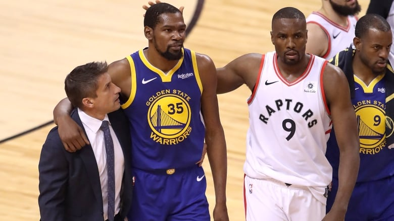 ff0f0c04a3e Kevin Durant, centre, is consoled by Raptors forward Serge Ibaka after the  Warriors star suffered an Achilles injury in Game 5 on Monday night.