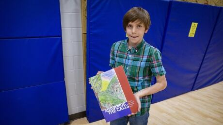 Grade 6 student Kalvin Keating with the book he and his classmates created on