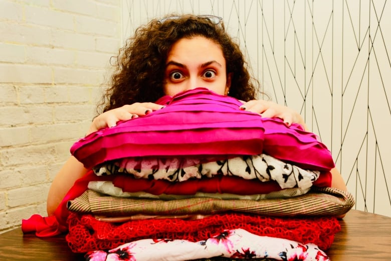 4bde66bbaa Emily Anas peeks out from behind a small pile of the 1,200 garments the  company has available for rental. (Tina Mackenzie/CBC)