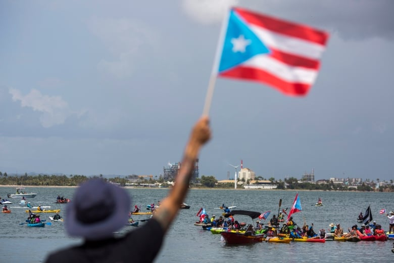 Demonstrators in kayaks gather in front of the governor's residence in San Juan on Sunday. (Dennis M. Rivera Pichardo/Associated Press)