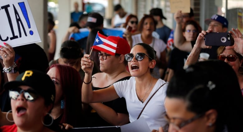 People from the Dallas-Fort Worth Puerto Rican community gather to protest Rossello outside the Adobo Puerto Rican Cafe in Irving, Texas, on Sunday. (Tom Fox/The Dallas Morning News via AP)