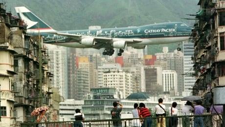 SIGHTSEERS AND PLANE LOVERS WATCH FINAL FLIGHTS AT HONG KONG'S KAI TAK AIRPORT.
