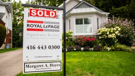 """House """"Sold"""" signs in Toronto real estate."""