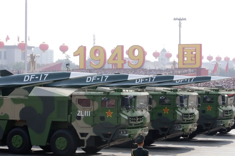 Military vehicles carrying hypersonic DF-17 missiles travel past Tiananmen Square during the parade. (Jason Lee/Reuters)