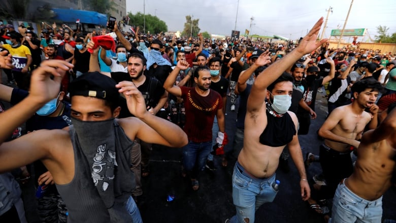 Iraqi police fire live rounds as protesters defy curfew amid anti-government protests