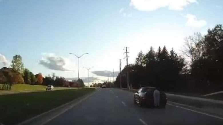 Halton police investigate 'shocking' video of someone hanging on a moving car