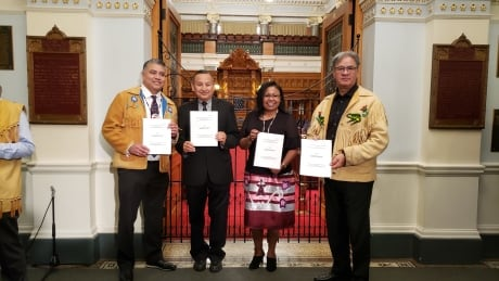 First Nations leadership hold printed copies of tabled legislation