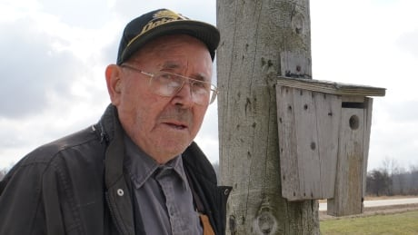 George Adams with one of his birdhouses
