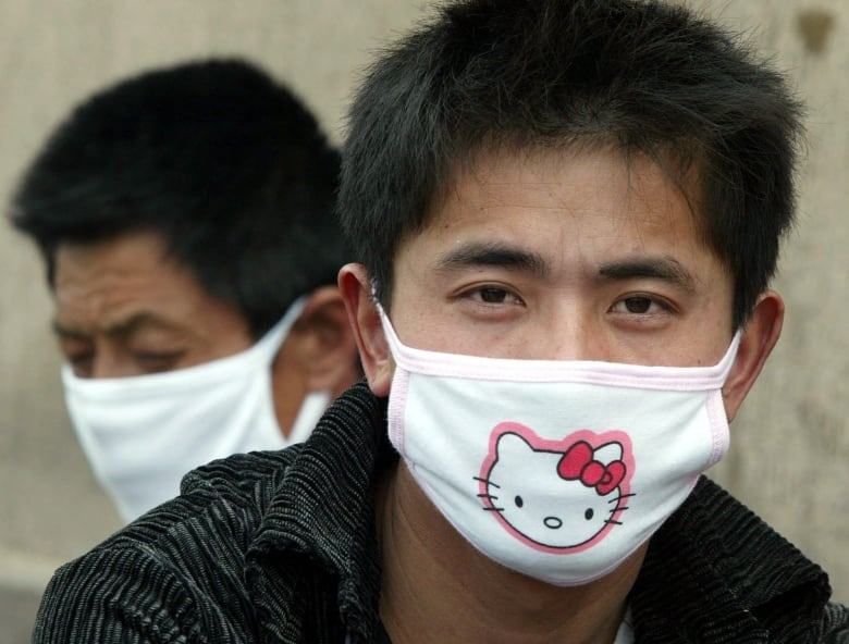 A man wears a mask to protect himself in Bejing during the 2003 SARS epidemic