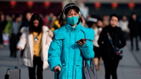 Traveller wearing a mask as SARS-like virus spreads in China