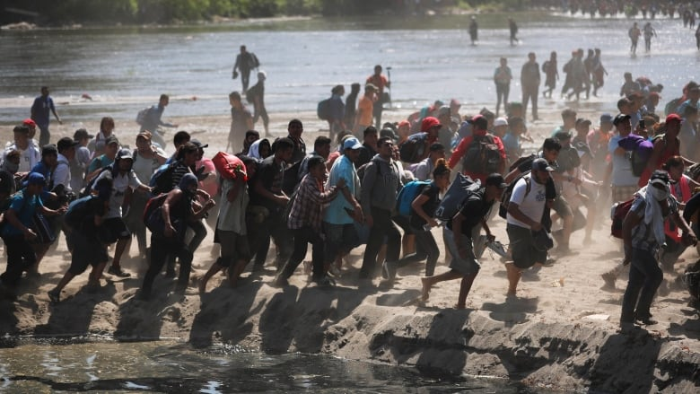 Hundreds of Central American migrants cross river into Mexico