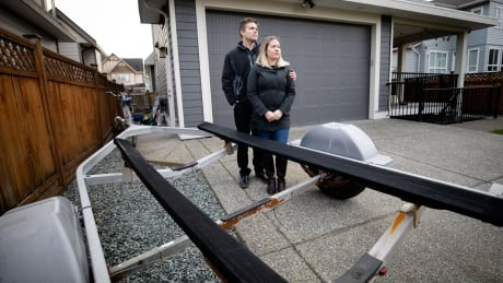 Matt and Justine Brown stand beside all they have left of their missing Bayliner- the boat trailer.