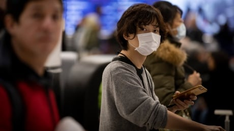 Passengers, and people waiting to pick them up, wear masks at Toronto Pearson International Airport on Sunday Jan. 26, 2019. The masks are a precaution against a coronavirus outbreak traced to Wuhan, China.