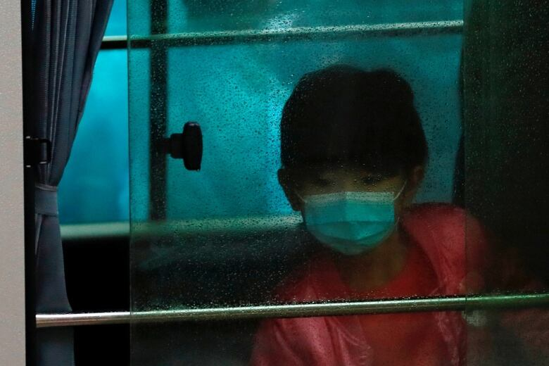 A child wears a face mask as she sits in a vehicle carrying residents evacuated from a public housing building in Hong Kong.(Tyrone Siu/Reuters)