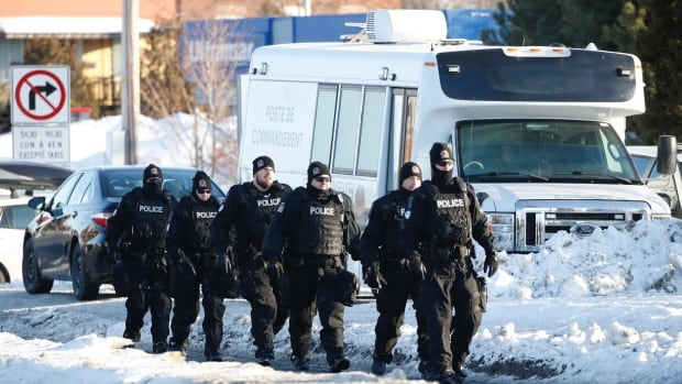 Police close street, back media away from protesters on CN rails in Saint-Lambert