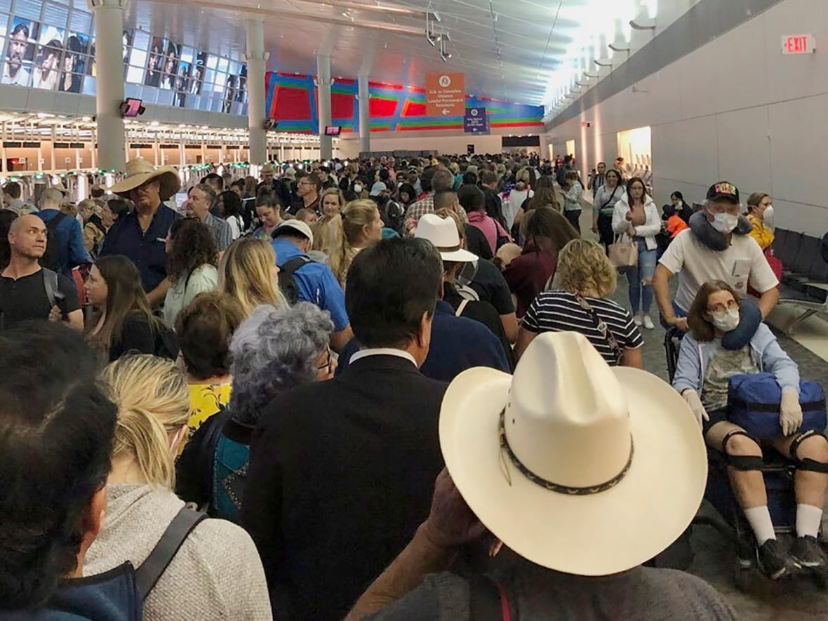 People wait in line to go through the customs at Dallas Fort Worth International Airport in Grapevine, Texas, on March 14, 2020.