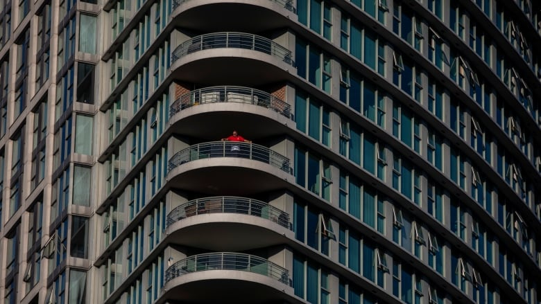 A man in a condo tower watches the sunset in downtown Vancouver on Friday. Advocacy groups have called for a moratorium on rent payments and evictions for the duration of the COVID-19 pandemic. (Ben Nelms/CBC)