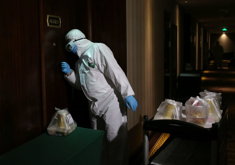 A worker in protective suit delivers meals at a hotel being used as a centralised observation and quarantine site for people arriving in China from overseas. (China Daily/Reuters)