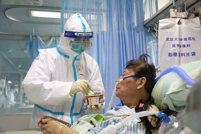A nurse in a protective suit feeds a novel coronavirus patient inside an isolated ward at Zhongnan Hospital of Wuhan University during the coronavirus lockdown of city. Nurses and doctors who were once silenced for warning about the coronavirus are now being celebrated. (China Daily/Reuters)