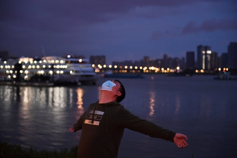 A man exercises at a riverside park by the Yangtze River in Wuhan Thursday. Life in the city is slowly getting back to normal, but people won't be able to leave the city that was the epicentre of China's coronavirus outbreak until April 8. (Stringer/Reuters)