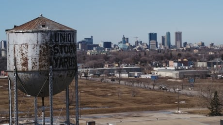The Old Union Stock Yards water tower standing before the Winnipeg city skyline