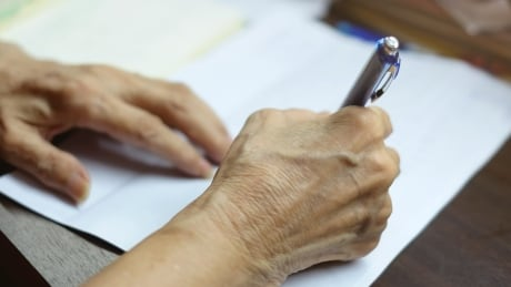 Elderly person signing document