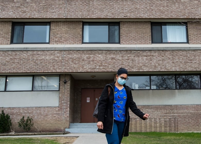A healthcare worker leaves after finishing her shift for the day at the Eatonville Care Centre in Toronto on Friday.