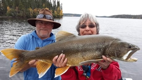 Guests at Kenanow Lodge hold up lake trout