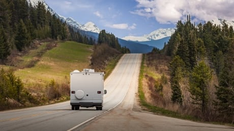 Tourists driving down the roads of the Canadian Rockies in an RV on a beautiful summer day