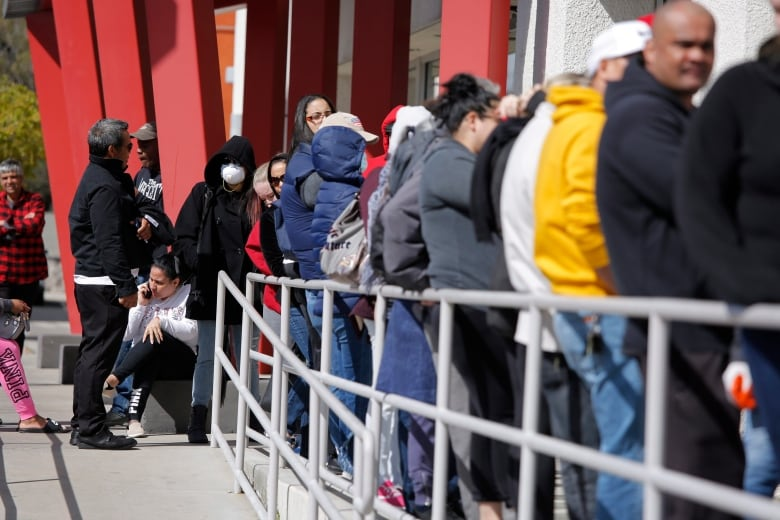 People wait in line for help with unemployment benefits in Las Vegas on March 17