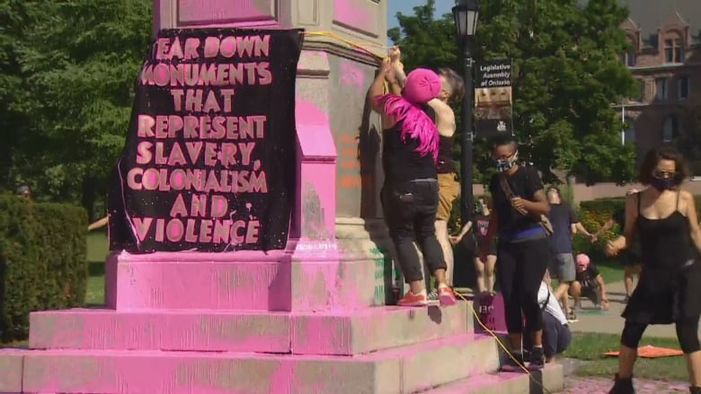 Police arrest 3 people after protesters splash paint on Toronto statues