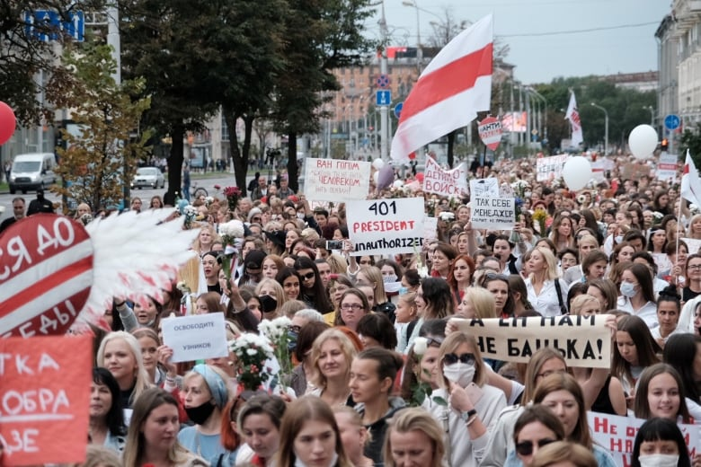 Hundreds of women dressed mostly in red and white — the colours of the former Belarusian flag that the opposition uses as an emblem — marched through Minsk on Saturday.(BelaPAN via Reuters)