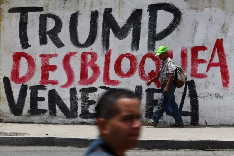 A mural displayed in Caracas in August 2019 reads in Spanish: 'Trump unblock Venezuela' after U.S. President Donald Trump signed an executive order freezing Venezuelan government assets in an escalation of tensions with Maduro. (Leonardo Fernandez/The Associated Press)