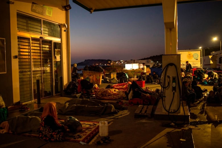 Homelesss migrants and refugees rest as they spend the night at a gas station near Mytilene