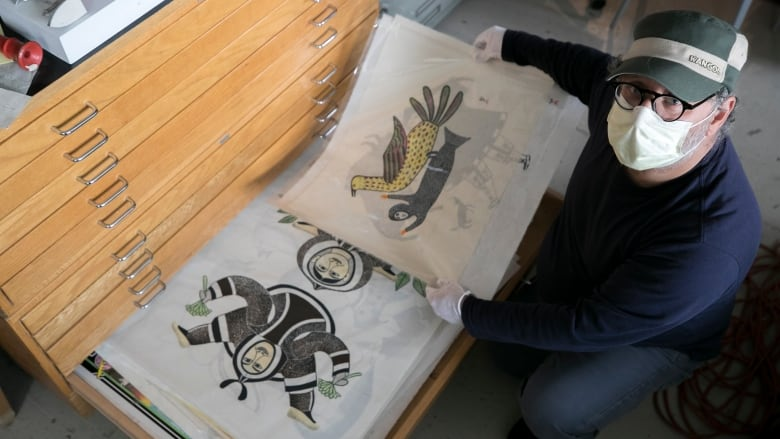 Gallery owner Adnan Charara holds Sedna with Spotted Bird by Lucy Qinnuayuak and Gathering Spring Plants by Egyvudluk Ragee — part of a trove of Inuit art recently found inside a dilapidated Detroit home. (Joe Gall)