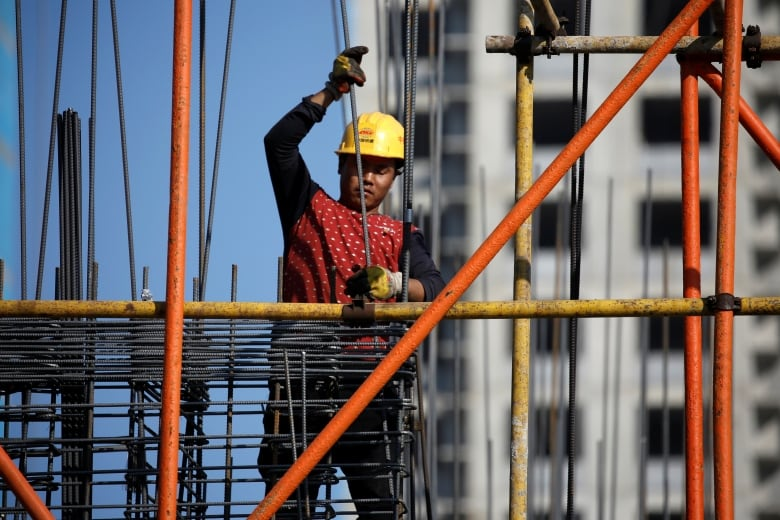 A worker is seen on scaffoldings at a construction site of a residential compound in Beijing on Monday
