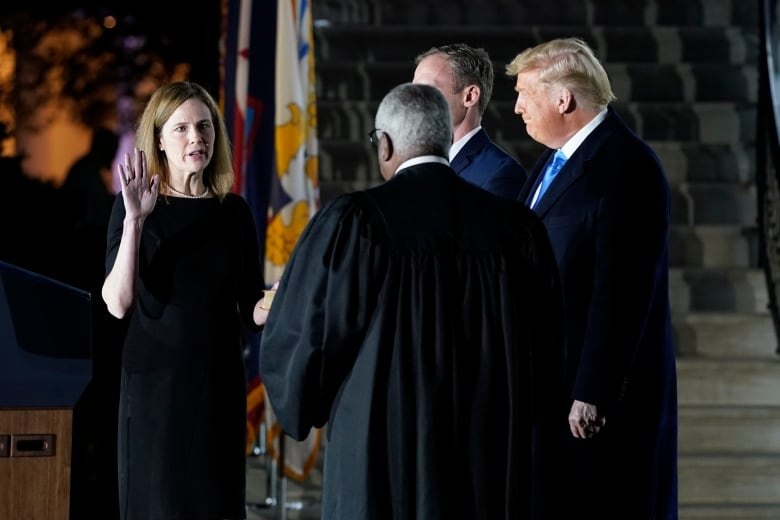 Barrett is administered the Constitutional Oath by Supreme Court Justice Clarence Thomas as Jesse M. Barrett and Trump look on. (Patrick Semansky/The Associated Press)