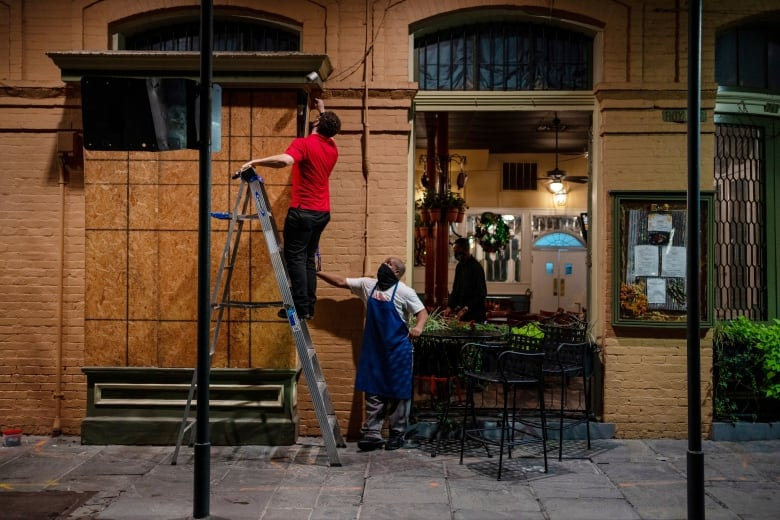 Restaurant workers board up windows on Tuesday as they prepare for the arrival of Zeta in New Orleans