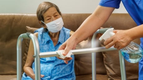 Shutterstock health-care aide cleaning walker of resident in mask