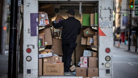 A FedEx employee sorts through multiple packages to be delivered in downtown Vancouver, British Colu
