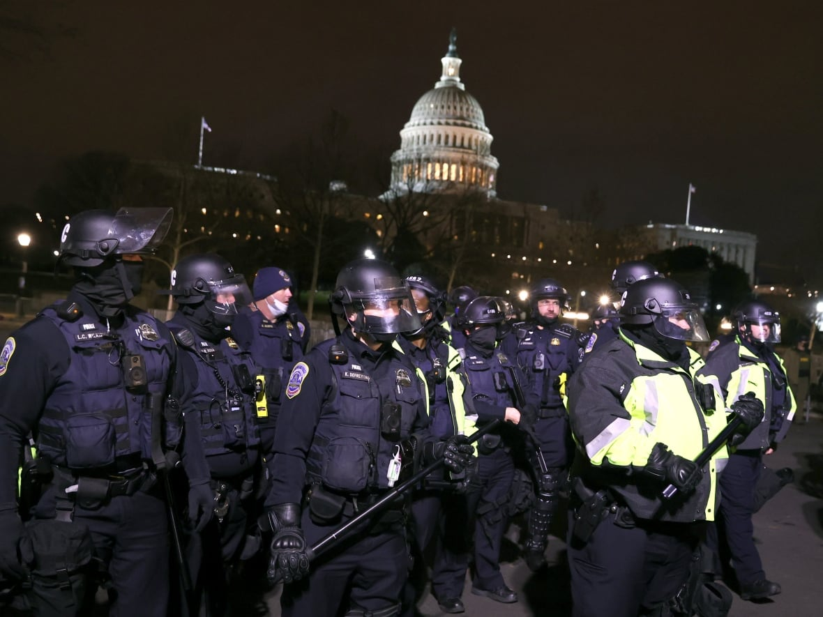 Police officers in riot gear monitor protesters gathered at the Capitol on Wednesday evening.