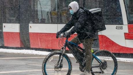 DSC02456: A delivery person on a bike in the snow