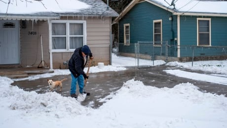 Man shovelling show in Waco, Texas on Feb. 17, 2021