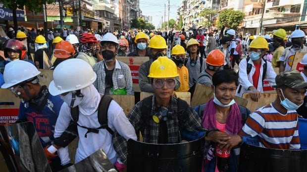 Defying deadly crackdown, protesters in hard hats and goggles clash with riot police in Myanmar | CBC News