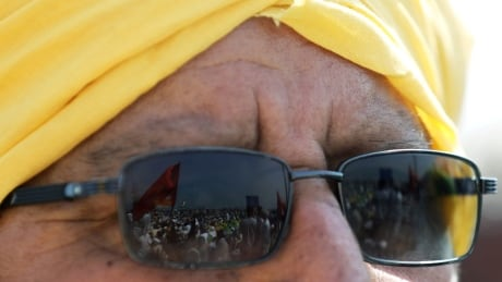 Farmers' protest action seen in reflection of a man's sunglasses in Haryana, India